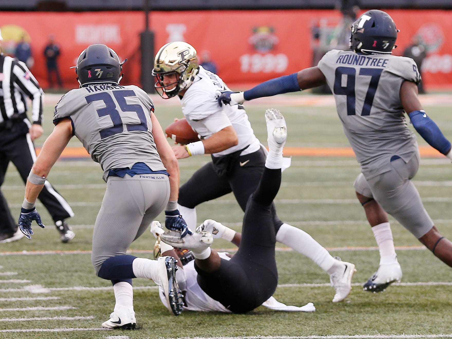 Purdue quarterback David Blough gets chased down by Jake Hansen and Bobby Roundtree of Illinois in the second half Saturday, October 13, 2018, in Champaign, Illinois. Purdue thumped Illinois 46-7.