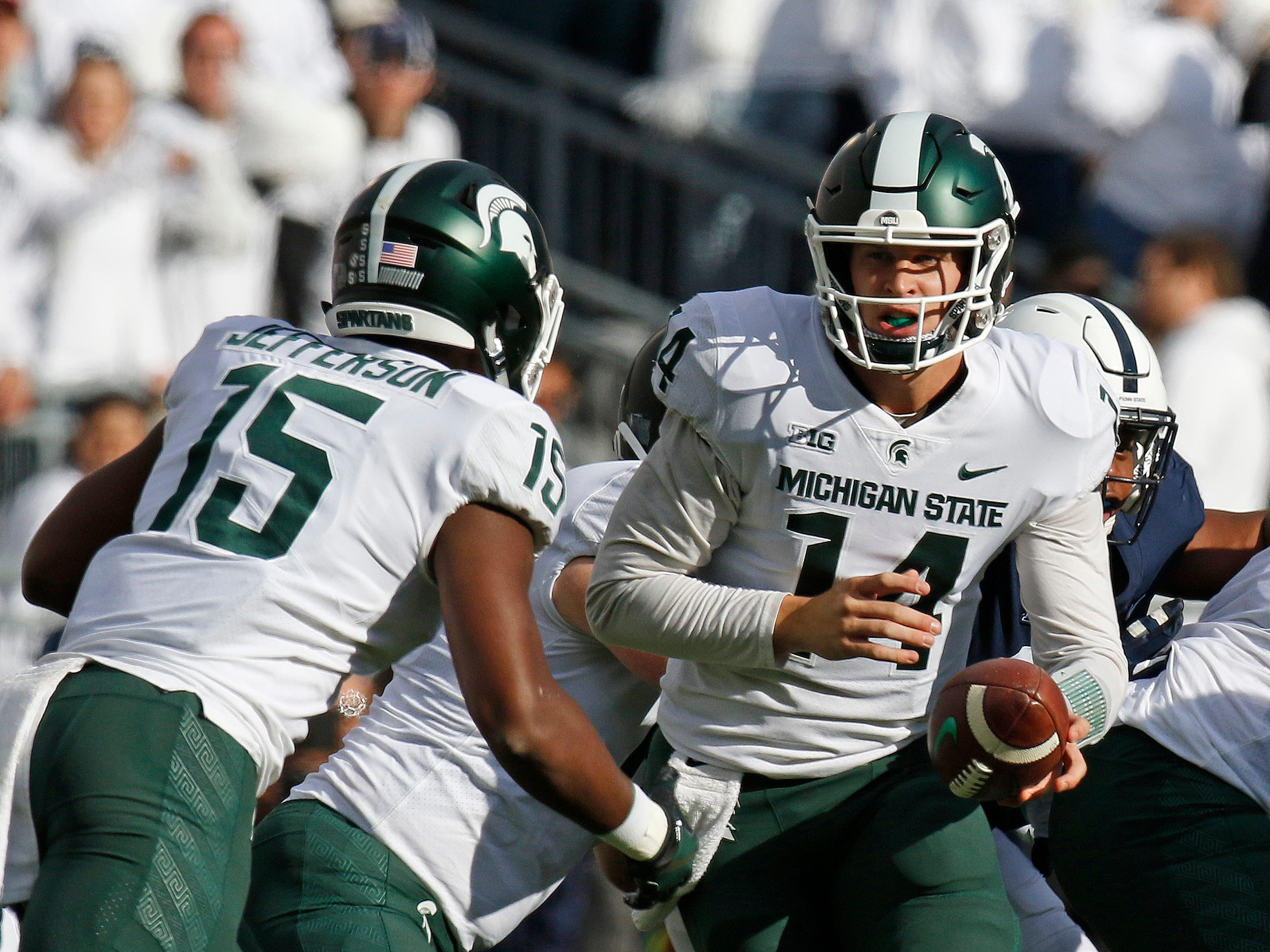 Brian Lewerke #14 of the Michigan State Spartans hands off to La'Darius Jefferson #15 of the Michigan State Spartans against the Penn State Nittany Lions on October 13, 2018 at Beaver Stadium in State College, Pennsylvania.