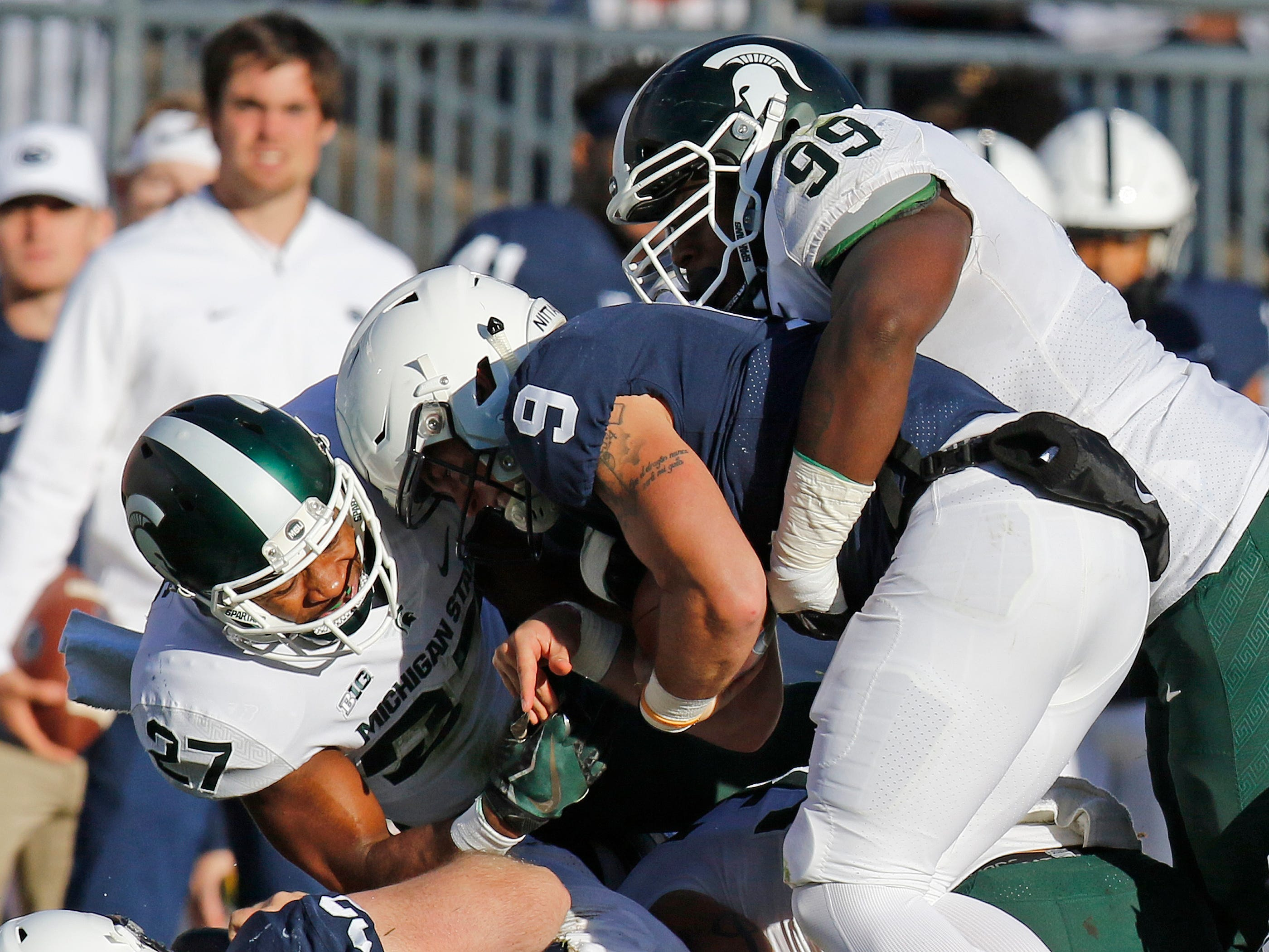 Khari Willis #27 of the Michigan State Spartans and Raequan Williams #99 of the Michigan State Spartans tackle Trace McSorley #9 of the Penn State Nittany Lions on October 13, 2018 at Beaver Stadium in State College, Pennsylvania.