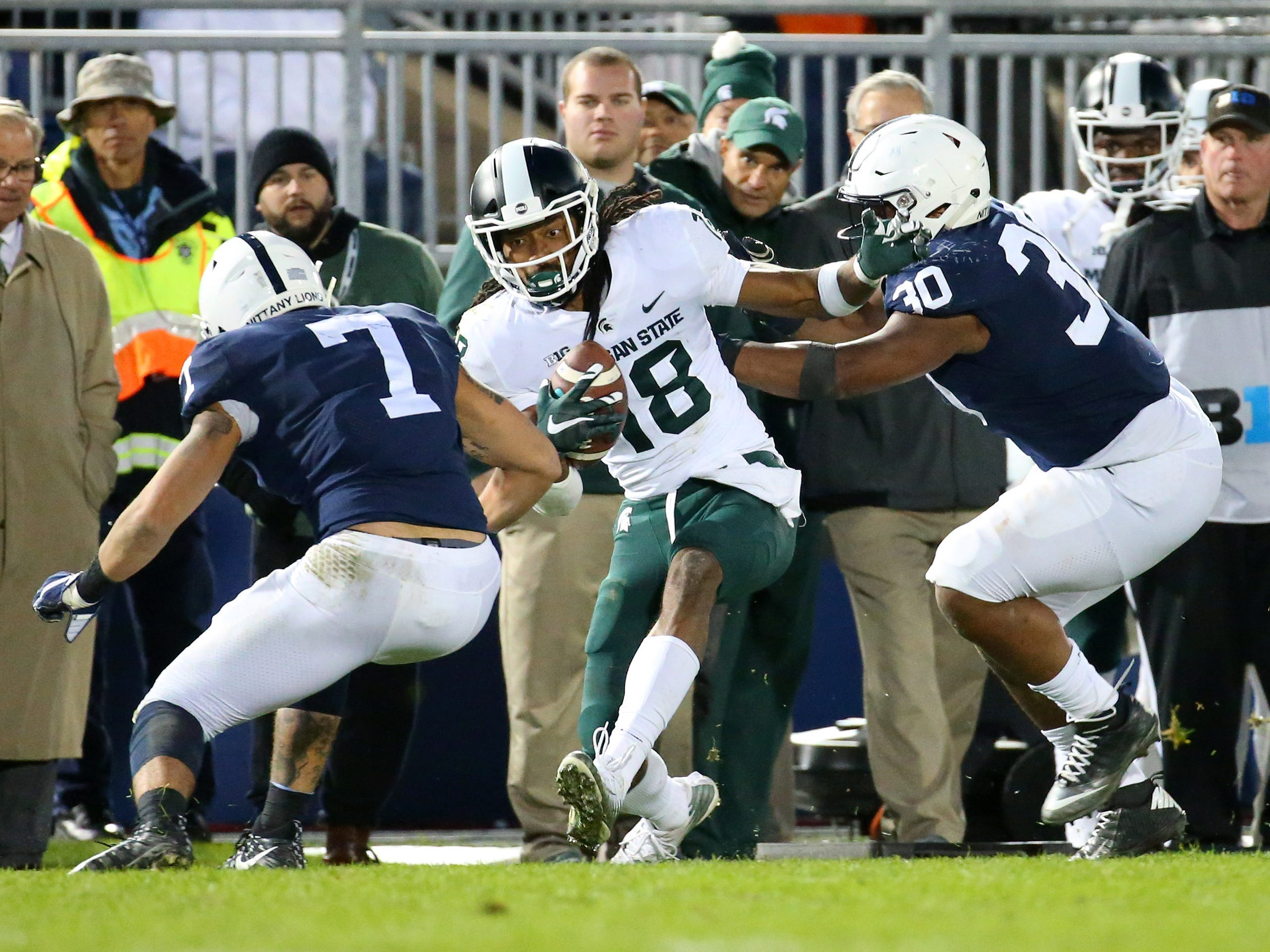 Michigan State Spartans wide receiver Felton Davis III (18) runs with the ball after a catch against Penn State Nittany Lions linebacker Koa Farmer (7) and defensive tackle Kevin Givens (30) during the fourth quarter at Beaver Stadium.