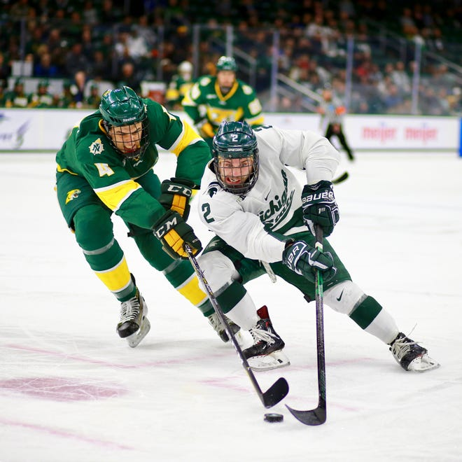 Michigan State defenseman Zach Osburn fights off Northern Michigan's Connor Frantti for a loose puck during MSU's 4-3 loss on Saturday night. The Spartans won't play again until Oct. 26 at Cornell.