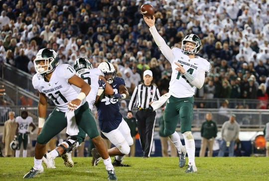 Michigan State Spartans quarterback Brian Lewerke (14) passes the ball for the winning touchdown to wide receiver Felton Davis III (not pictured) against the Penn State Nittany Lions during the fourth quarter at Beaver Stadium.