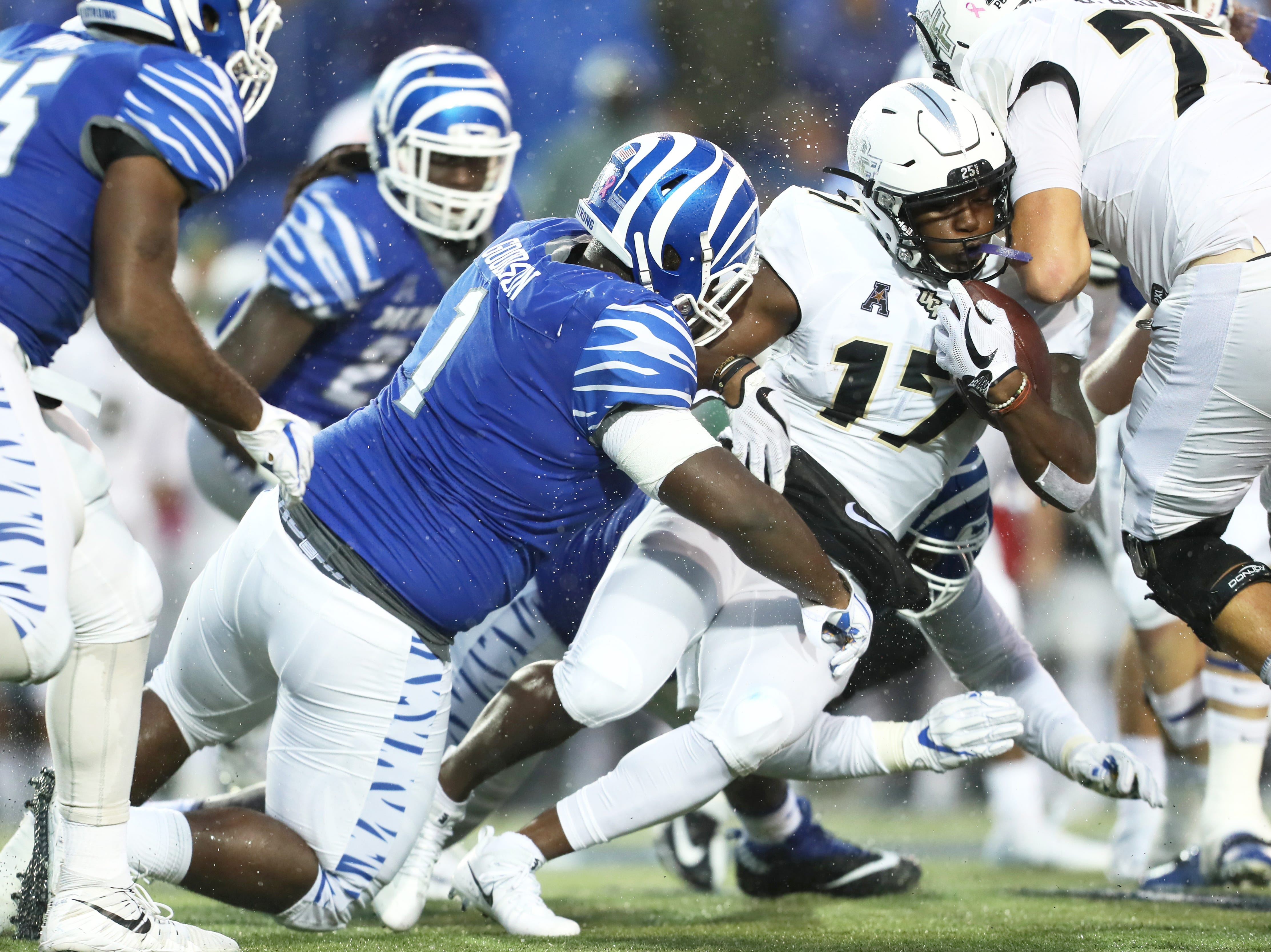 UCF's Marlon Williams drags along Memphis' O'Bryan Goodson for a first down during their game at the Liberty Bowl in Memphis, Tenn., Saturday, October 13, 2018.