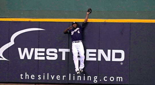 Brewers centerfielder Lorenzo Cain takes a home run away from the Dodgers' David Freese with a leaping catch against the wall in the first inning of Game 2 of the NLCS on Saturday afternoon.