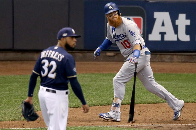 Justin Turner of the Dodgers hits a two-run homer against Jeremy Jeffress of the Brewers during the eighth inning in Game 2 of the NLCS at Miller Park on Saturday.