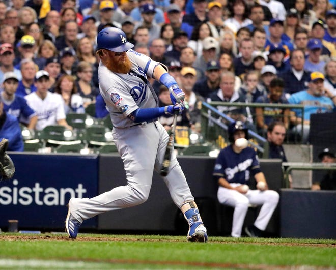 Justin Turner of the Dodgers turns on a pitch from Brewers reliever Jeremy Jeffress and sends it into the bleachers in left field for a two-run home run in the eighth inning of Game 2 on Saturday.
