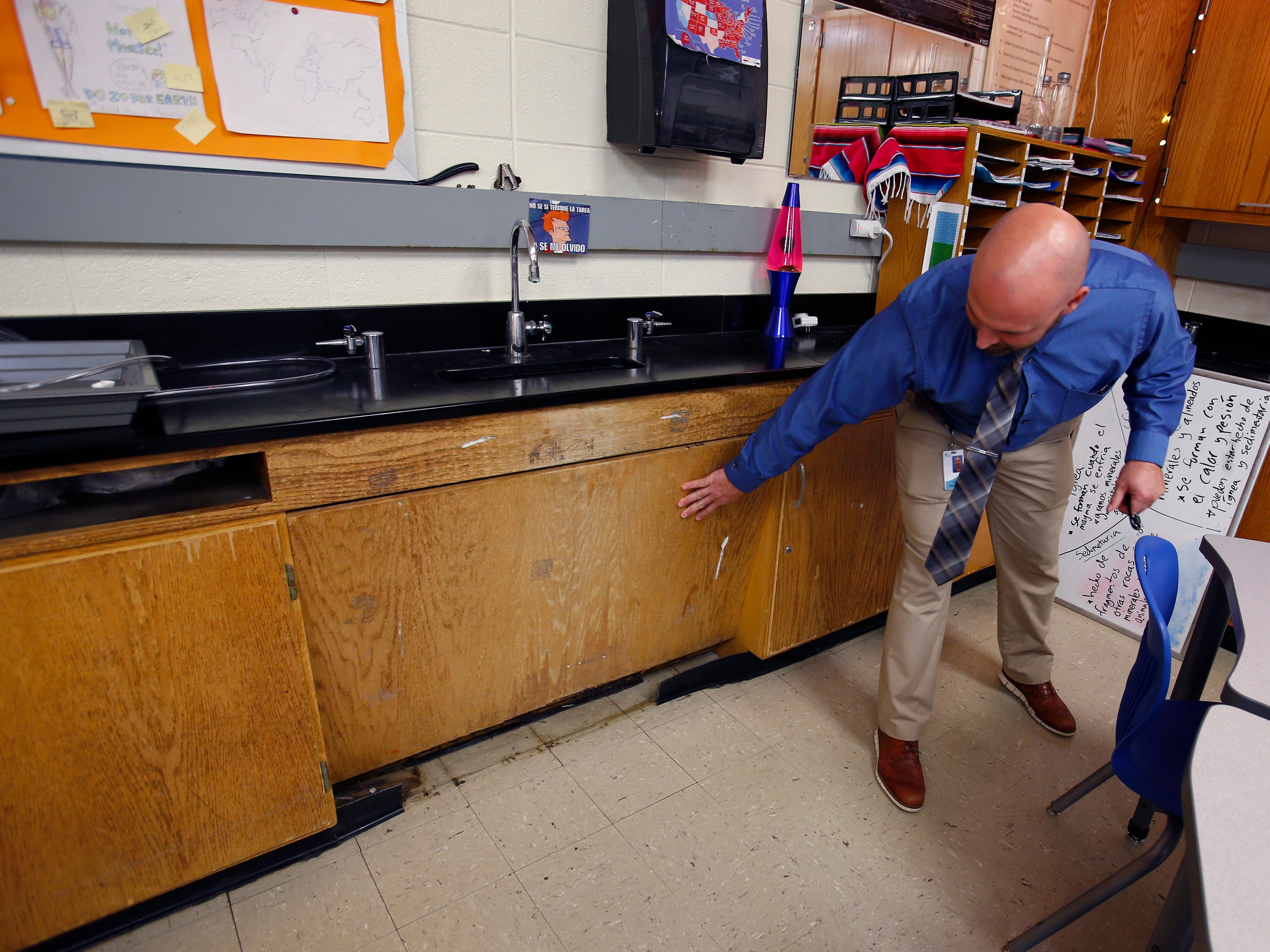 Principal Jason Sadowski shows the poor condition of cabinets within a science lab at Butler Middle School. The lab would be renovated as part of the $60 million school  referendum on the Nov. 6 ballot.