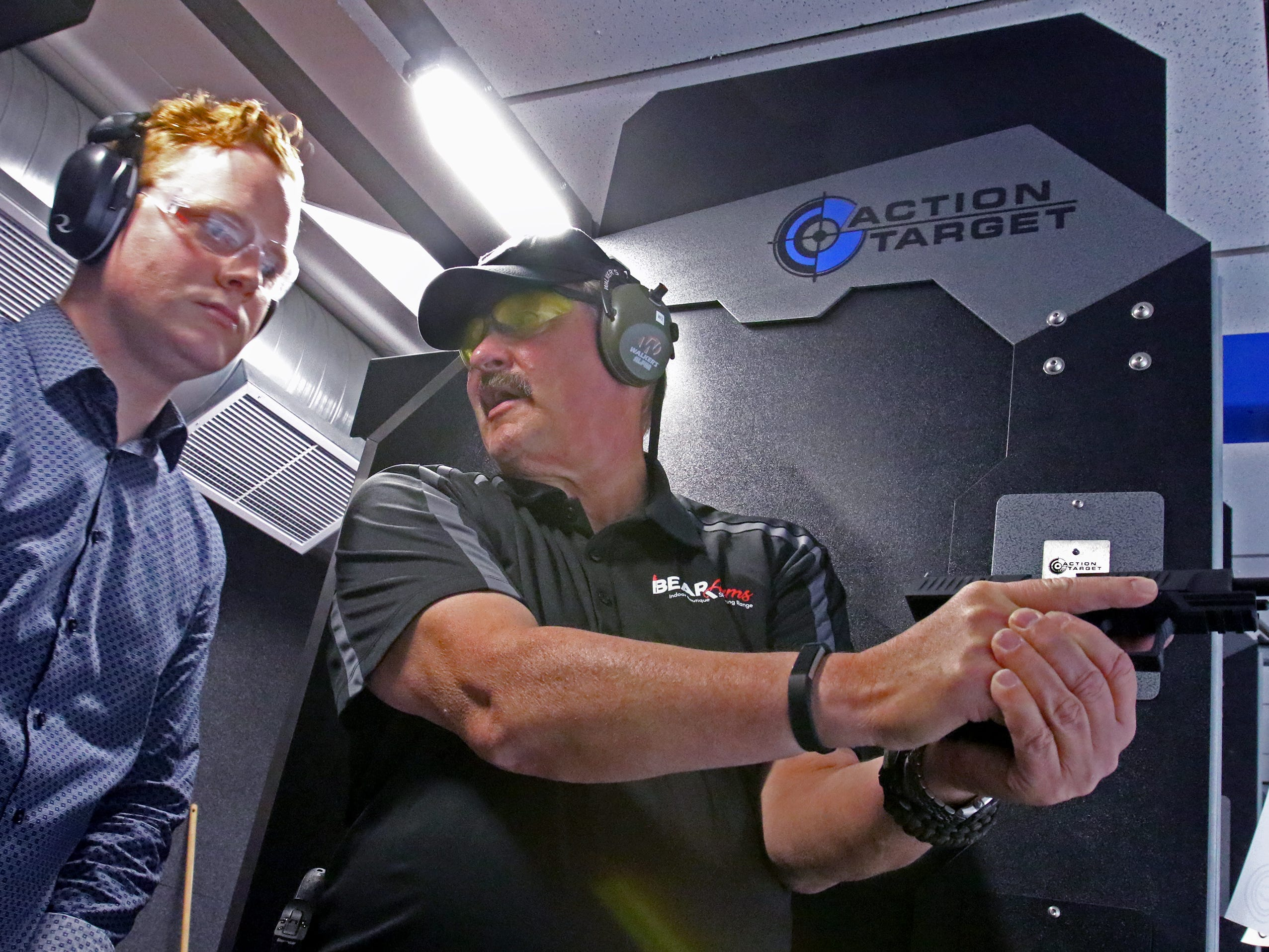 Mark Wierzbinski, a NRA certified firearms instructor, teaches Jeff Rummage, a NOW reporter, on the proper way to handle and discharge a semi-automatic handgun in one of the Bear Arms eight firing range lanes on Oct. 11.