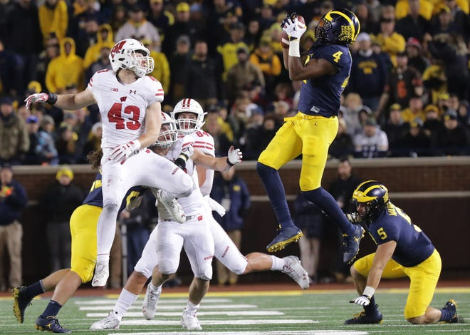 Michigan wide receiver Nico Collins recovers an onside kick attempt by the Badgers during the fourth quarter Saturday night.