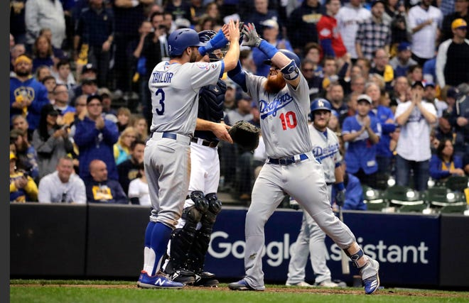 Justin Turner (10) is greeted by teammate Chris Taylor after he hit a two-run homer against the Brewers in the eighth inning that gave the Dodgers the lead for good in Game 2 of the NLCS on Saturday.