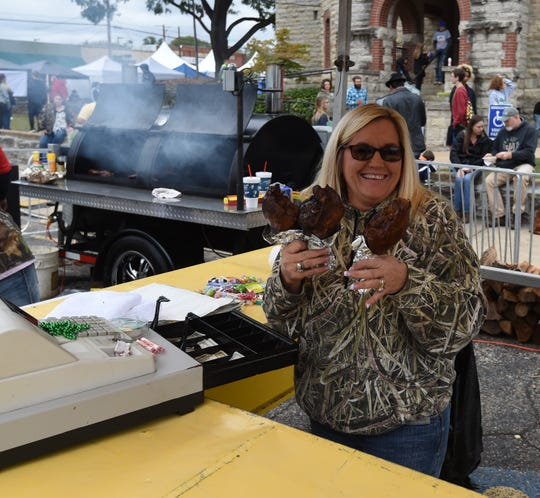 Sandra Johnson holds three turkey legs Saturday at the Johnson's Concessions booth at the 73rd annual Turkey Trot Festival.