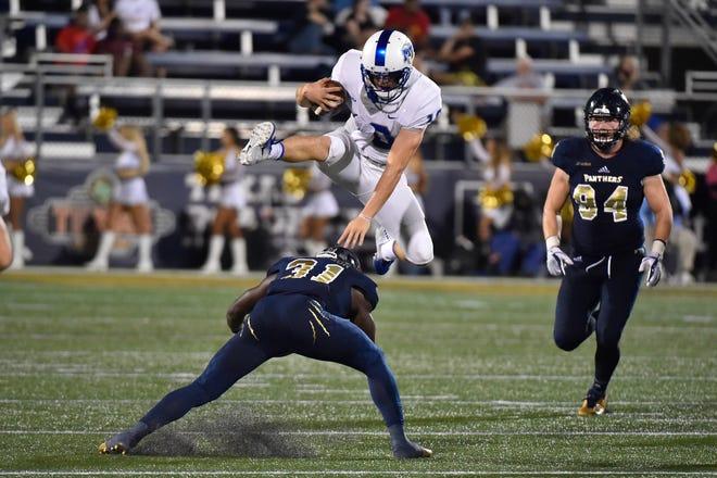 MTSU quarterback Asher O'Hara hurdles a Florida International defender during the Blue Raiders' 24-21 loss Saturday.
