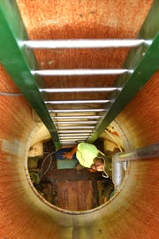 A worker looks up from inside a sewage lift station in Bolivar, Tenn. to check that all the pumps are working properly.