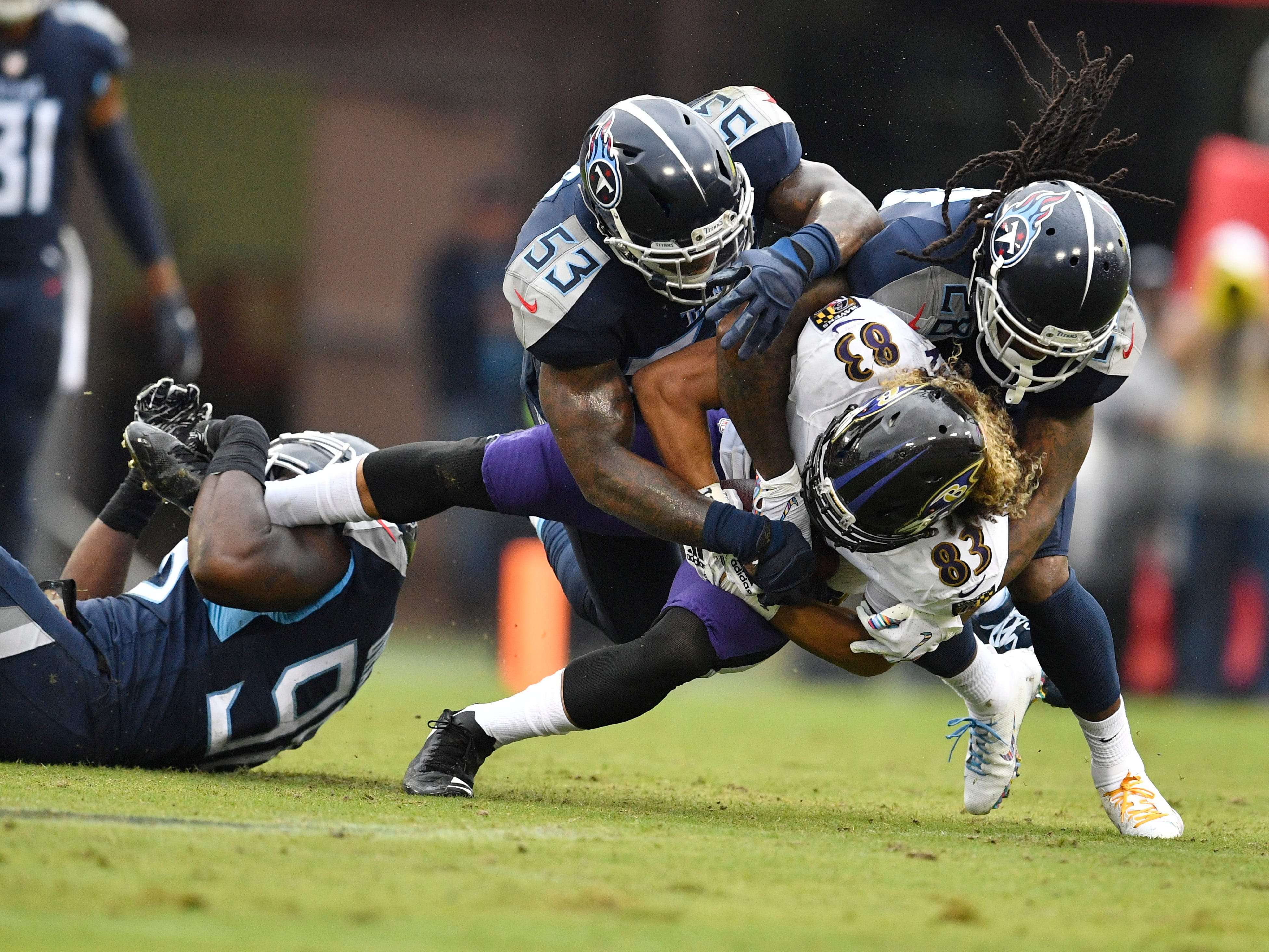 Titans linebacker Brian Orakpo (98), linebacker Daren Bates (53) and defensive back Kendrick Lewis (28) bring down Ravens wide receiver Willie Snead (83) in the first half at Nissan Stadium Sunday, Oct. 14, 2018, in Nashville, Tenn.