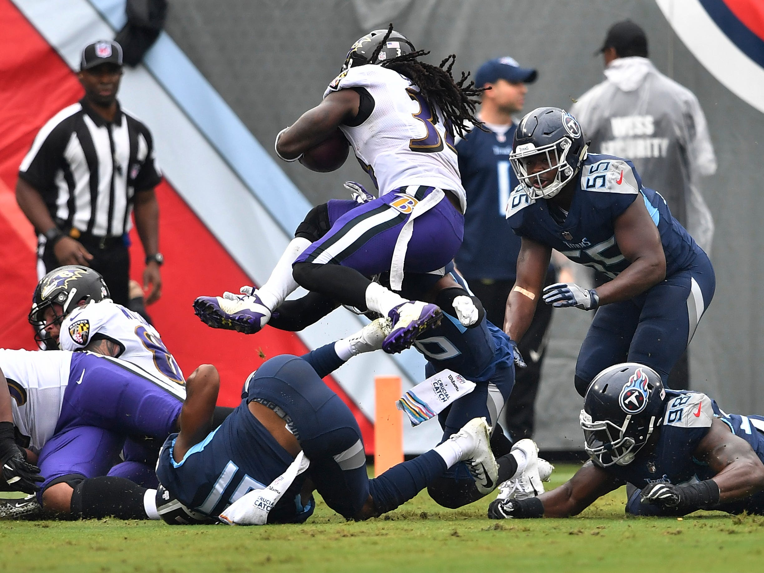 Ravens running back Alex Collins (34) goes up to gain yards in the first quarter at Nissan Stadium Sunday, Oct. 14, 2018, in Nashville, Tenn.