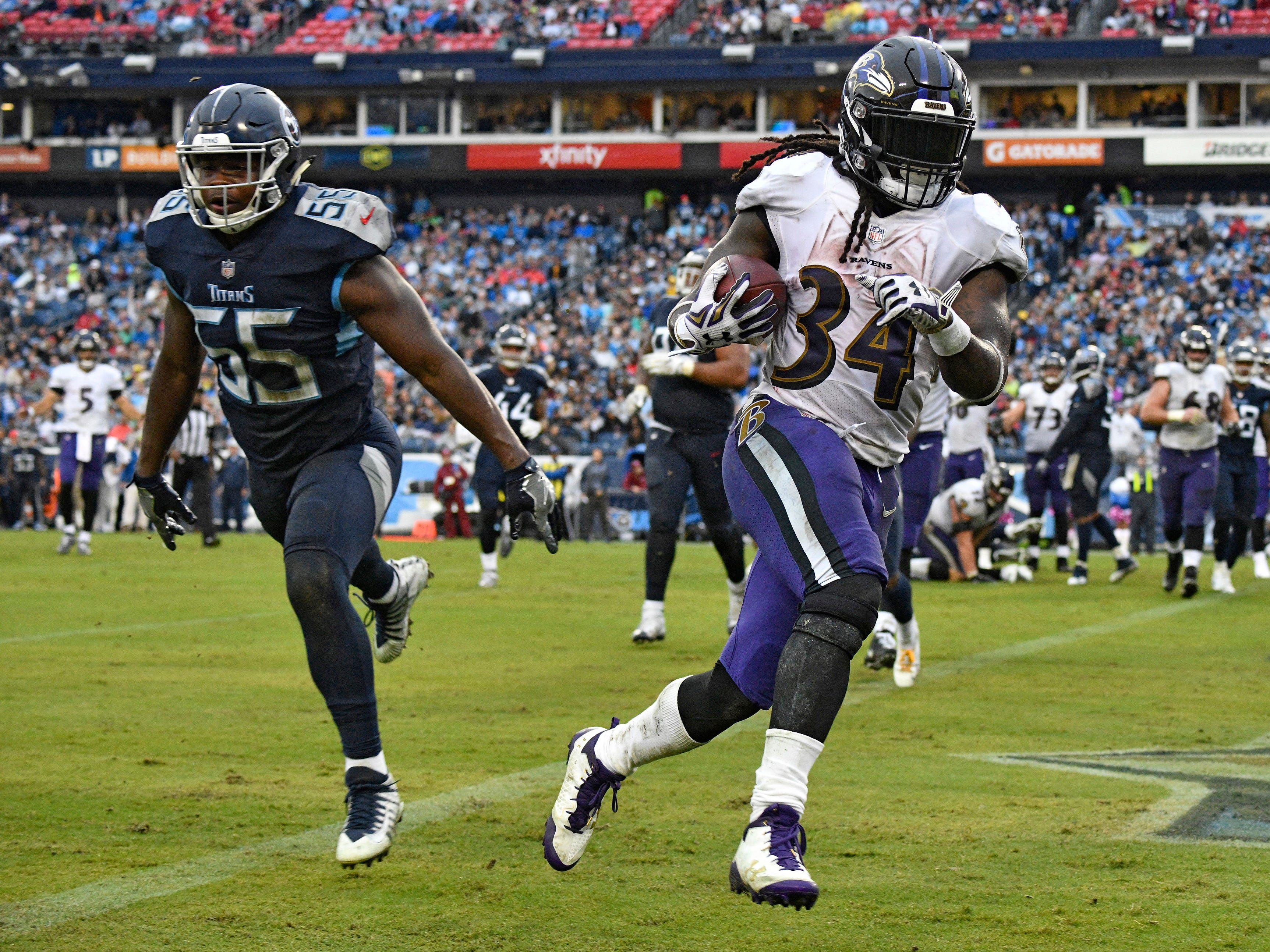 Ravens running back Alex Collins (34) gets by Titans linebacker Jayon Brown (55) for his second touchdown of the game during the third quarter at Nissan Stadium Sunday, Oct. 14, 2018, in Nashville, Tenn.