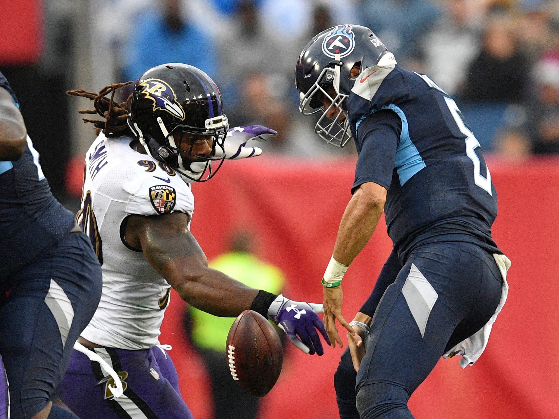 Ravens linebacker Za'Darius Smith (90) strips the ball from Titans quarterback Marcus Mariota (8) who recovered his own fumble in the second quarter at Nissan Stadium Sunday, Oct. 14, 2018, in Nashville, Tenn.