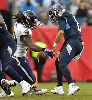 Ravens linebacker Za'Darius Smith (90) strips the ball from Titans quarterback Marcus Mariota (8), who recovered his own fumble, in the second quarter Sunday.