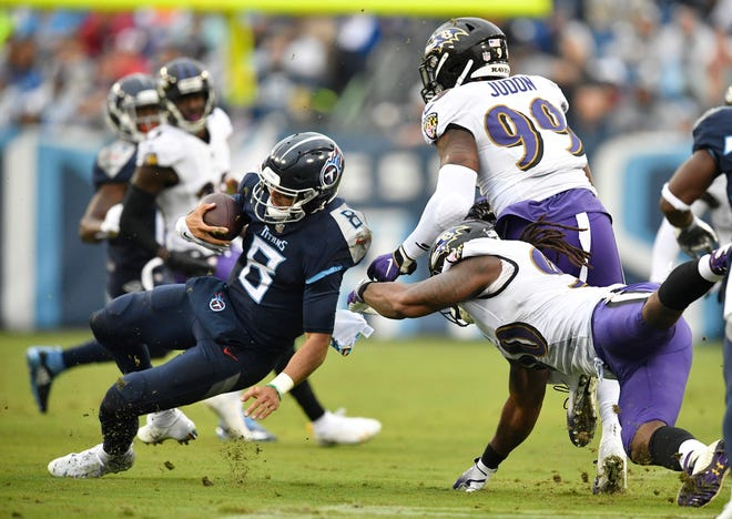 Titans quarterback Marcus Mariota (8) goes down in the first half Sunday.