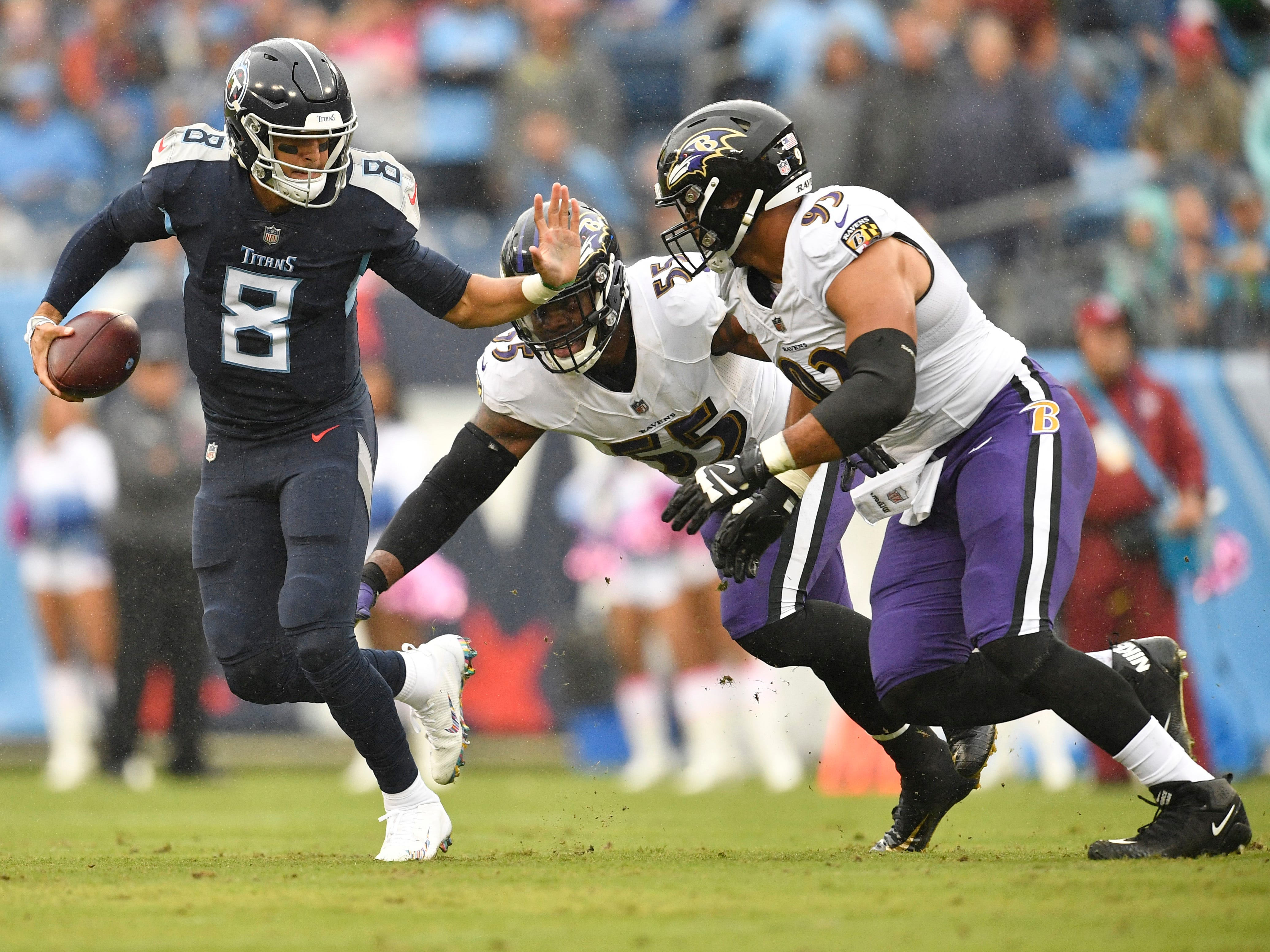 Titans quarterback Marcus Mariota (8) tries to scramble away from Ravens linebacker Terrell Suggs (55) and  defensive end Chris Wormley (93) in the first quarter at Nissan Stadium Sunday, Oct. 14, 2018, in Nashville, Tenn.