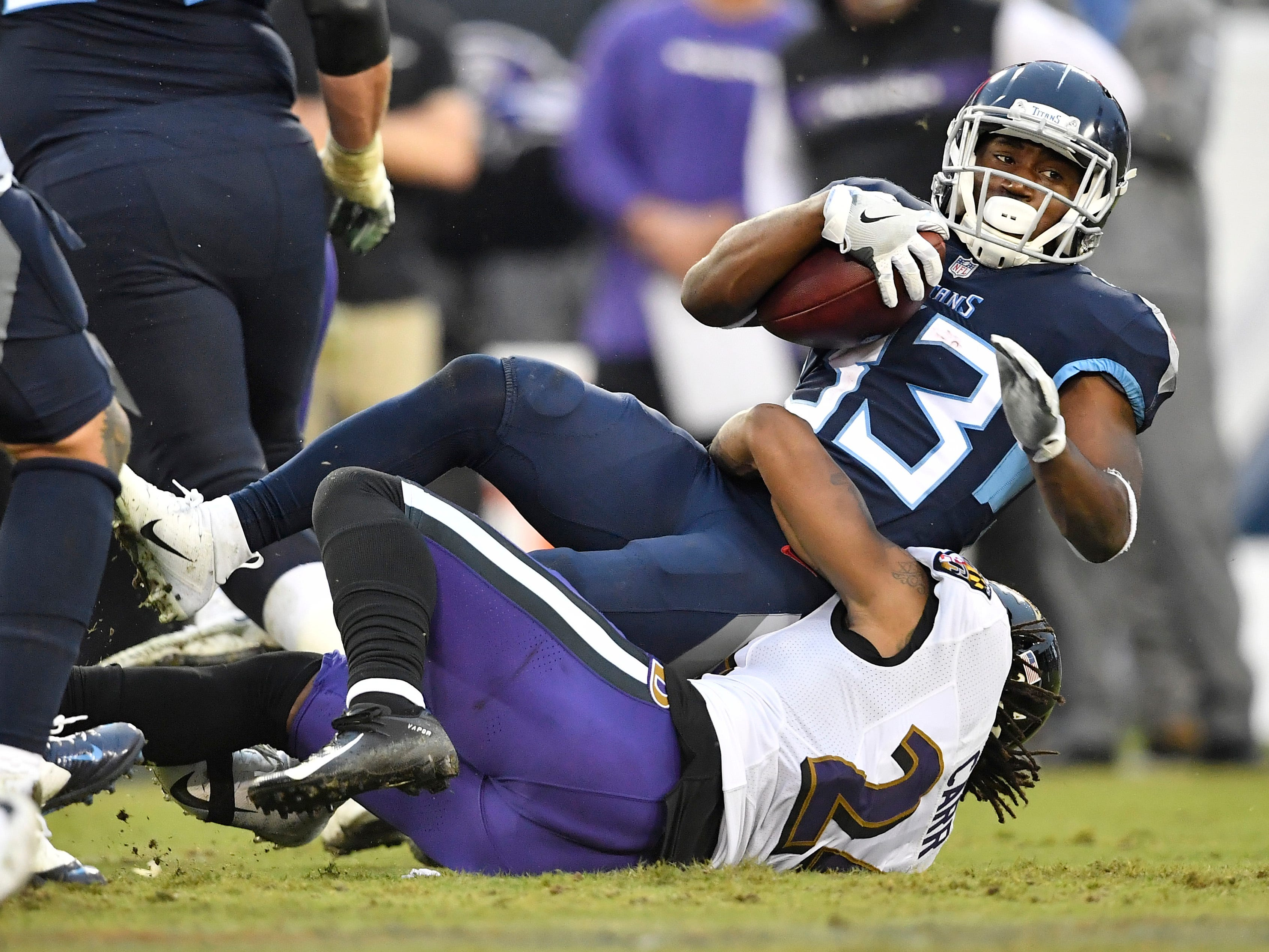 Titans running back Dion Lewis (33) gets stopped by Ravens cornerback Brandon Carr (24) in the third quarter at Nissan Stadium Sunday, Oct. 14, 2018, in Nashville, Tenn.