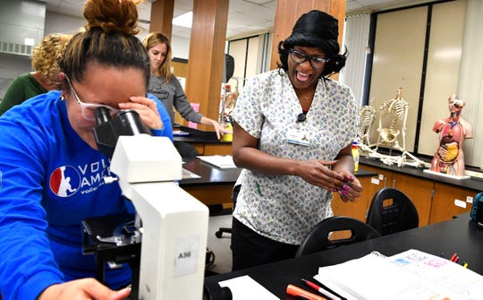 Sheeteah Blair looks on as a fellow student examines tissue samples during an anatomy class at Nashville State on Oct. 4.