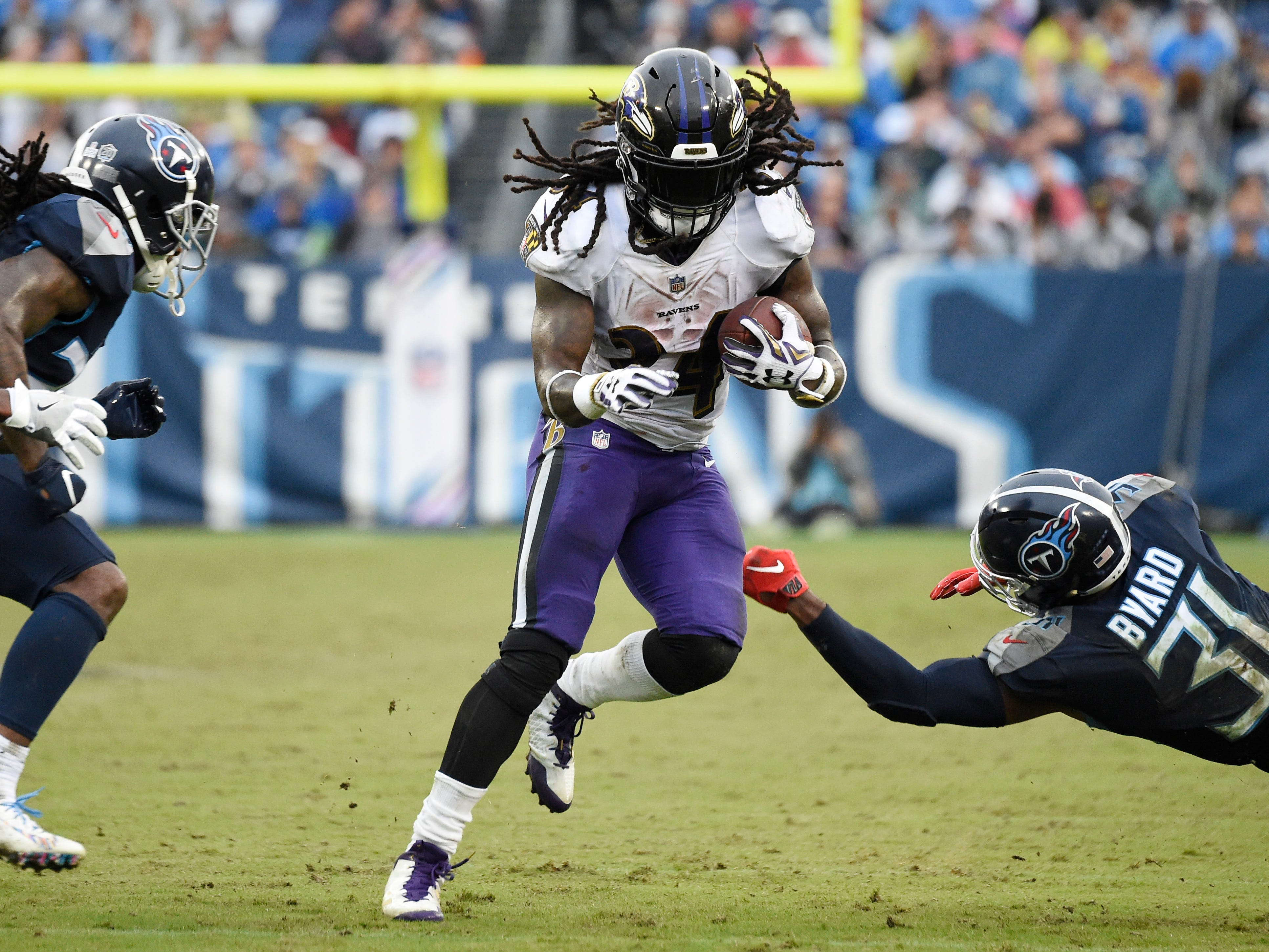 Ravens running back Alex Collins (34) breaks away from Titans free safety Kevin Byard (31) in the third quarter at Nissan Stadium Sunday, Oct. 14, 2018, in Nashville, Tenn.
