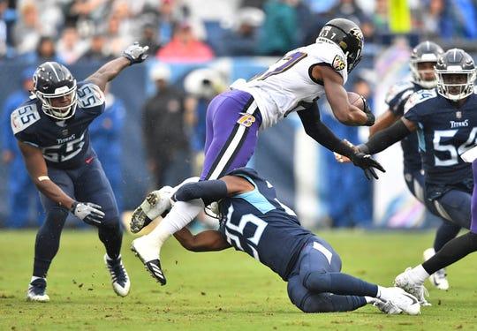 Titans cornerback Adoree' Jackson (25) brings down Ravens running back Javorius Allen (37) in the first quarter at Nissan Stadium Sunday, Oct. 14, 2018, in Nashville, Tenn.