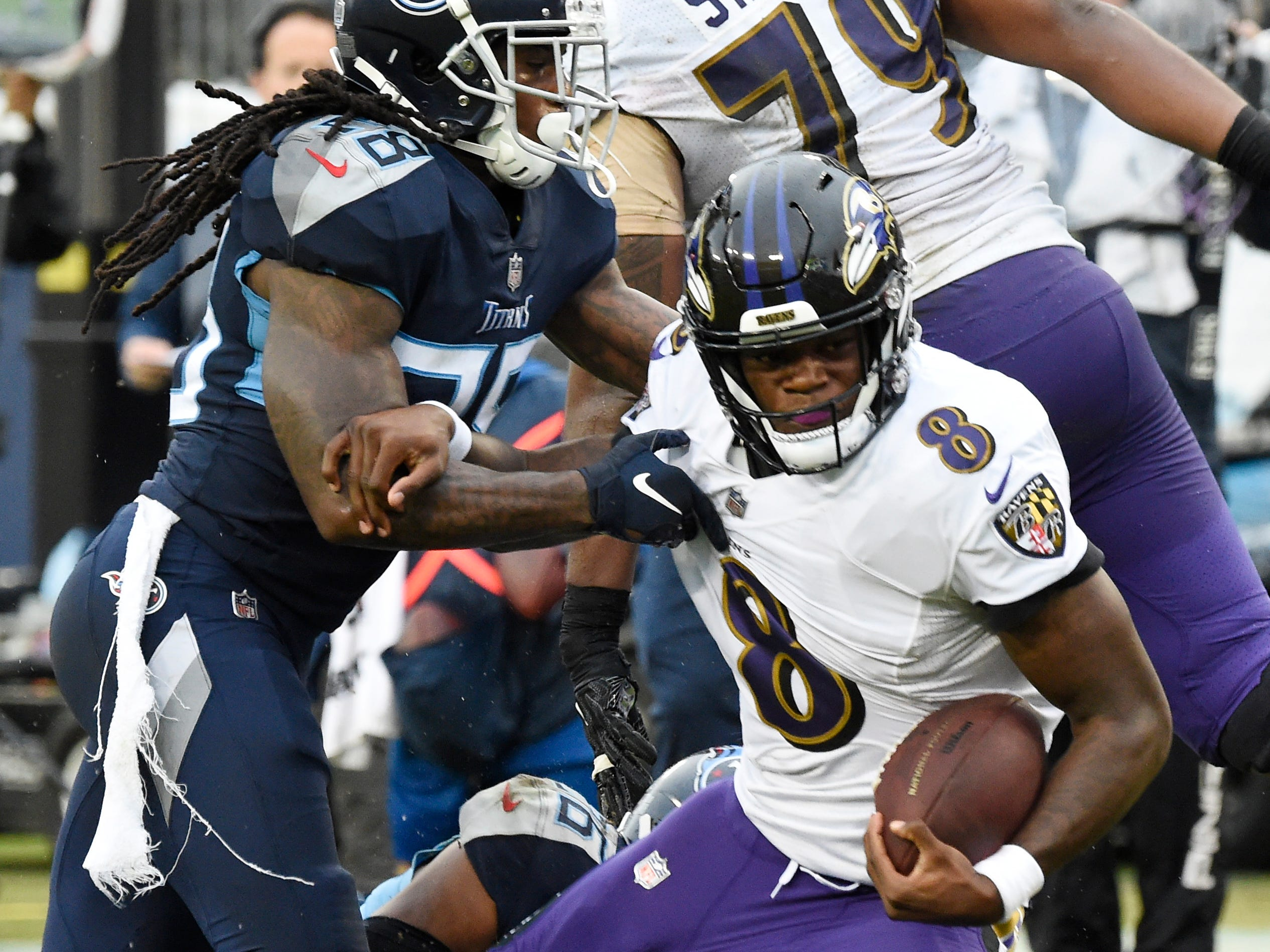 Ravens quarterback Lamar Jackson (8) gets a first down defended by Titans defensive back Kendrick Lewis (28) in the third quarter at Nissan Stadium Sunday, Oct. 14, 2018, in Nashville, Tenn.