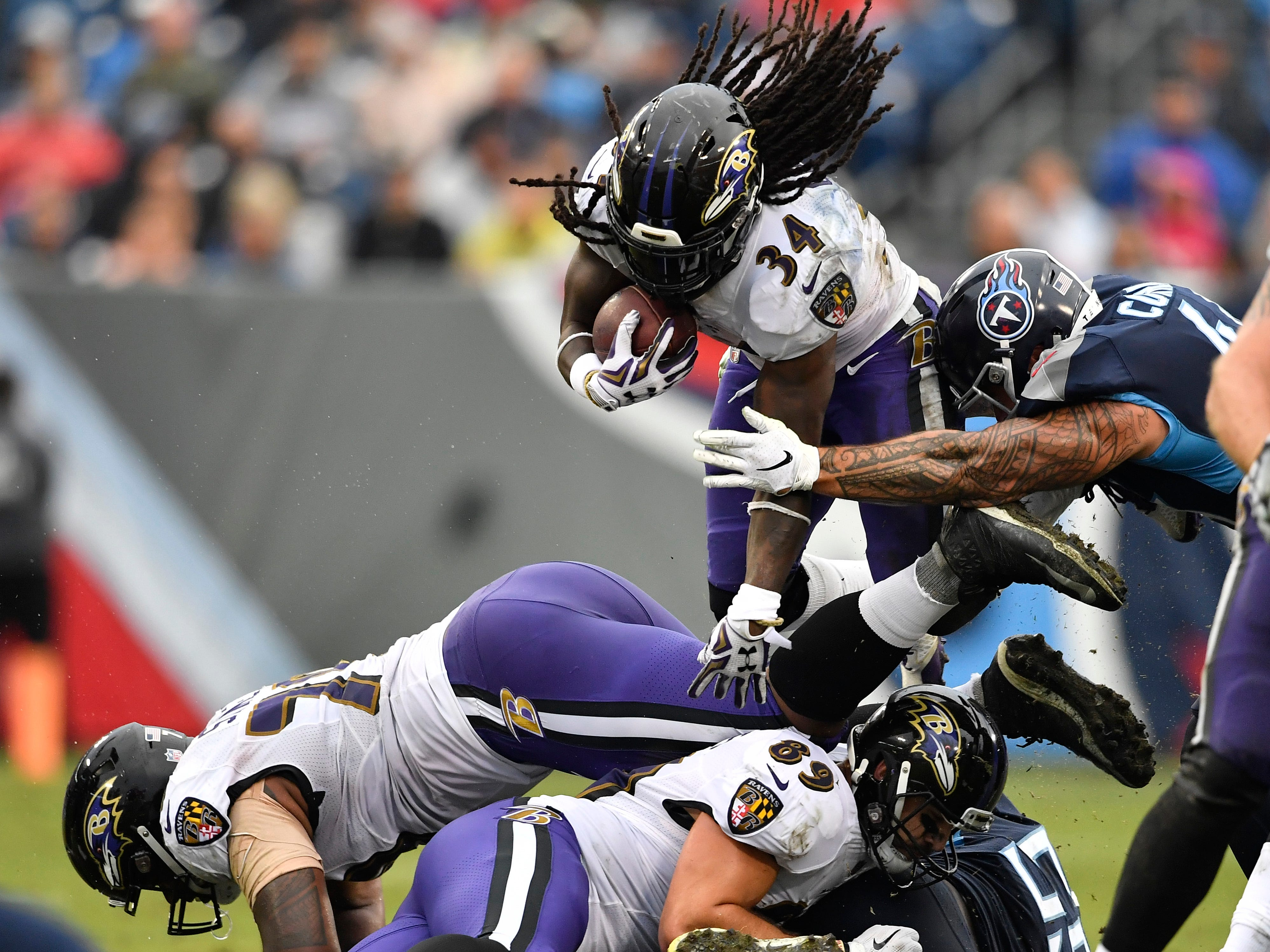 Ravens running back Alex Collins (34) leaps over Titans defenders in the third quarter at Nissan Stadium Sunday, Oct. 14, 2018, in Nashville, Tenn.