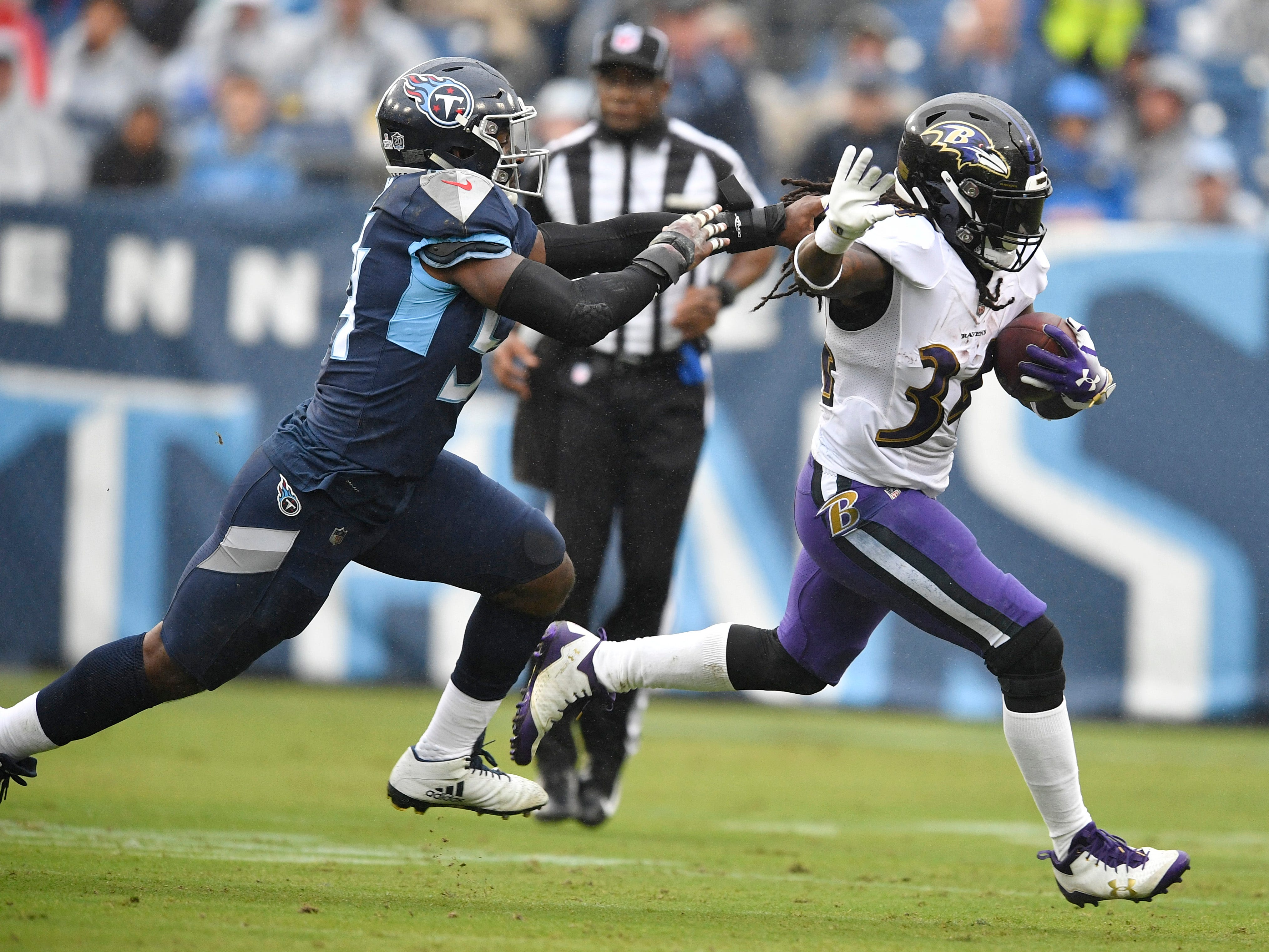 Ravens running back Alex Collins (34) gains yards defended by Titans linebacker Rashaan Evans (54) in the first quarter at Nissan Stadium Sunday, Oct. 14, 2018, in Nashville, Tenn.