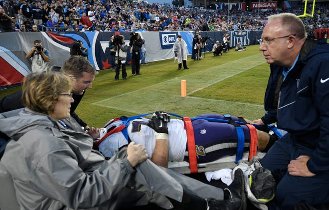 Ravens guard Alex Lewis (72) is carted off the field to a waiting ambulance during the fourth quarter Sunday.