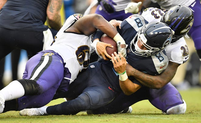 Ravens defensive tackle Willie Henry (69) and strong safety Tony Jefferson (23) sack Titans quarterback Marcus Mariota (8) in the third quarter Sunday.