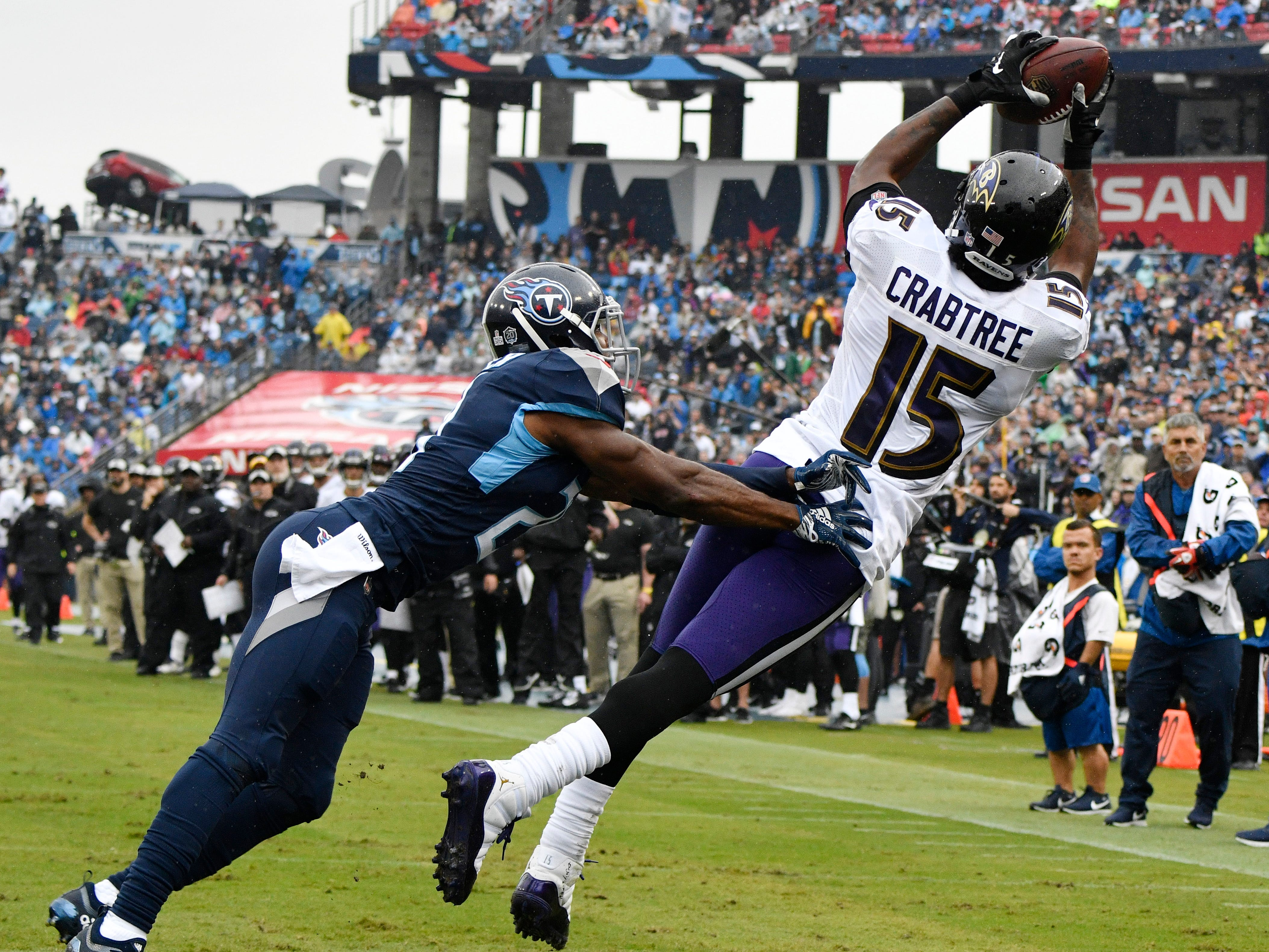Ravens wide receiver Michael Crabtree (15) catches a touchdown pass defended by Titans cornerback Malcolm Butler (21) in the first quarter at Nissan Stadium Sunday, Oct. 14, 2018, in Nashville, Tenn.