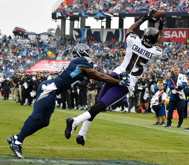 Ravens wide receiver Michael Crabtree (15) catches a touchdown pass defended by Titans cornerback Malcolm Butler (21) in the first quarter Sunday.
