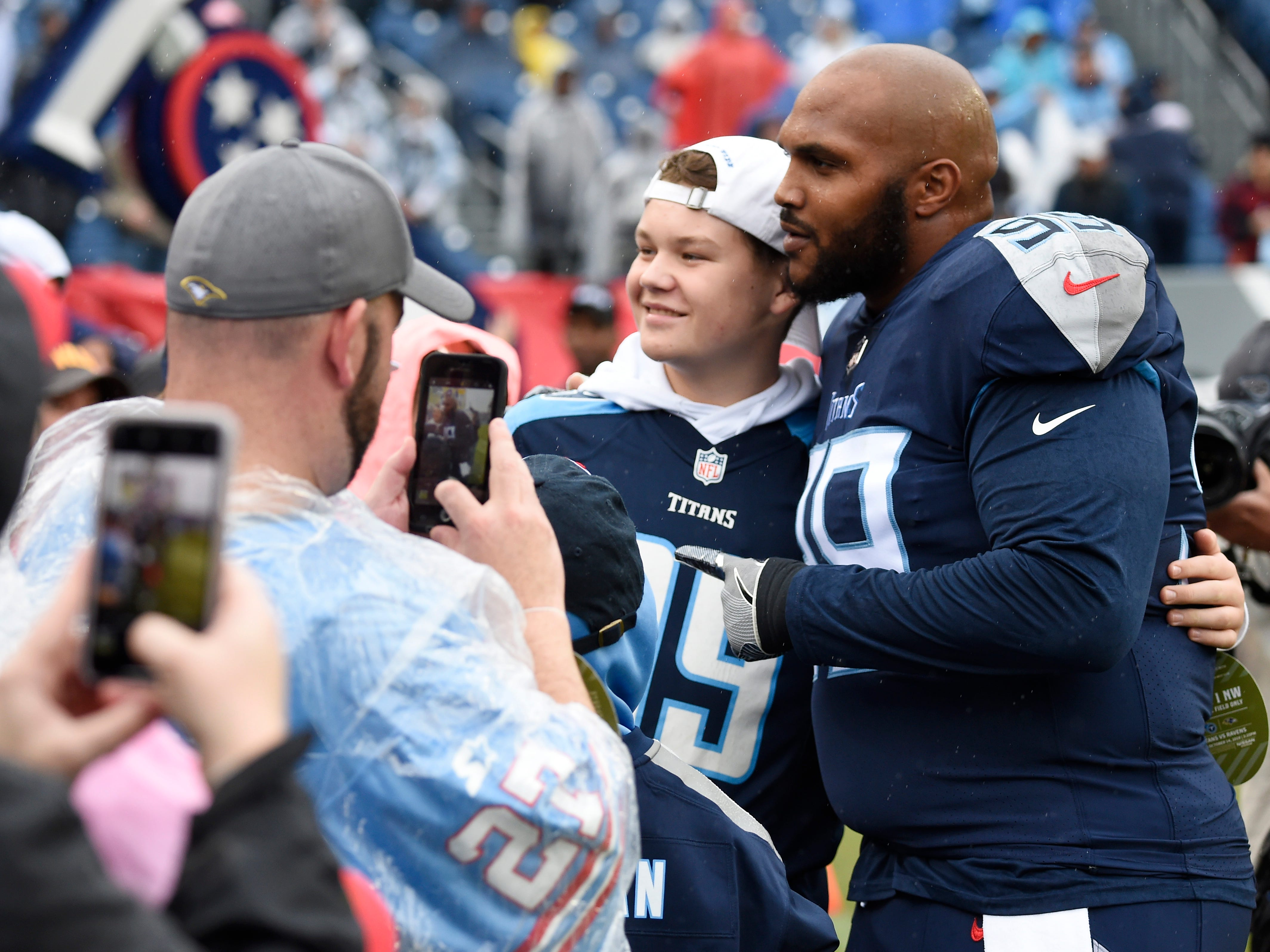 Titans defensive tackle Jurrell Casey (99) poses for a photo with a fan before the game at Nissan Stadium Sunday, Oct. 14, 2018, in Nashville, Tenn.