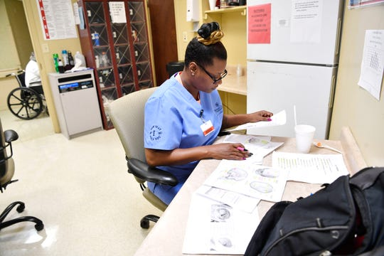 Sheeteah Blair does homework during a break at her job at Bethany Healthcare Center.