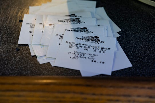 Lost bet tickets lie atop the bar counter at Naples Fort Myers Greyhound Racing & Poker on Friday, Oct. 12, 2018.