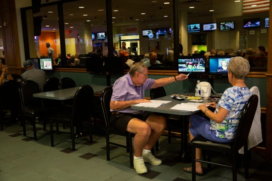 """Donald Schaller, on the left, and his wife, Gail Schiller of Fort Myers, watches the Keeneland horse race at  Naples Fort Myers Greyhound Racing & Poker on Friday afternoon, Oct. 12, 2018. The couple originally hail from Cincinnati, Ohio, and feel strongly about watching and betting on the race as they have for 31 years of their lives. """"It is better than watching television,"""" Donald said."""