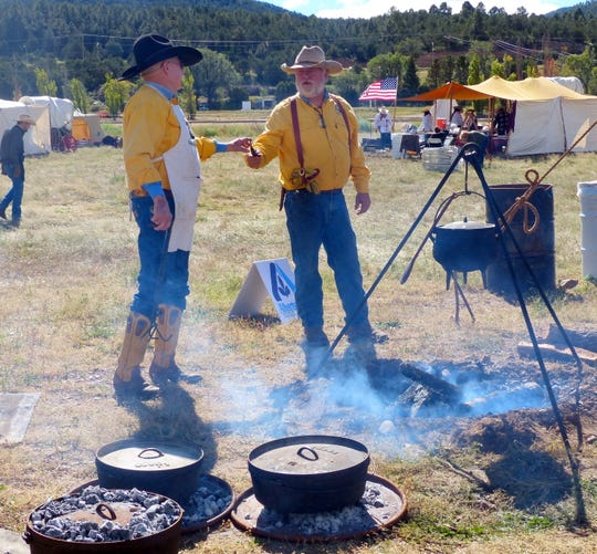Chuckwagon cooks tend dutch ovens topped with hot embers during a previous Lincoln County Cowboy Symposium.