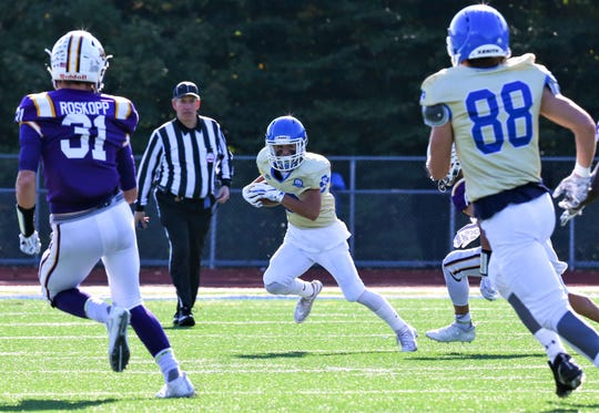 Catholic Central's Cody Daraban (middle) goes for the punt return in front of teammate Joshua Kipp (88) and DeLaSalle's Derek Roskopp (31).