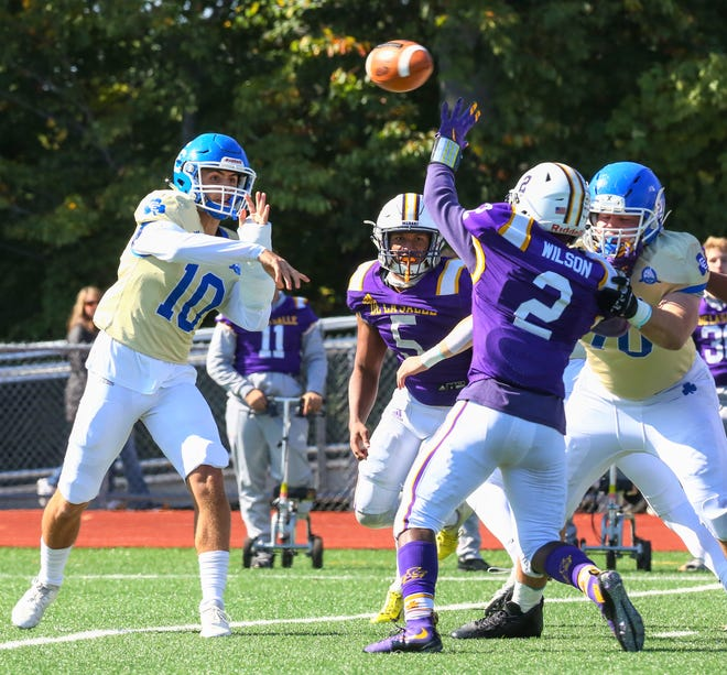 Catholic Central QB Marco Genrich (10) makes the pass over DeLaSalle defender Dylan Wilson (2).