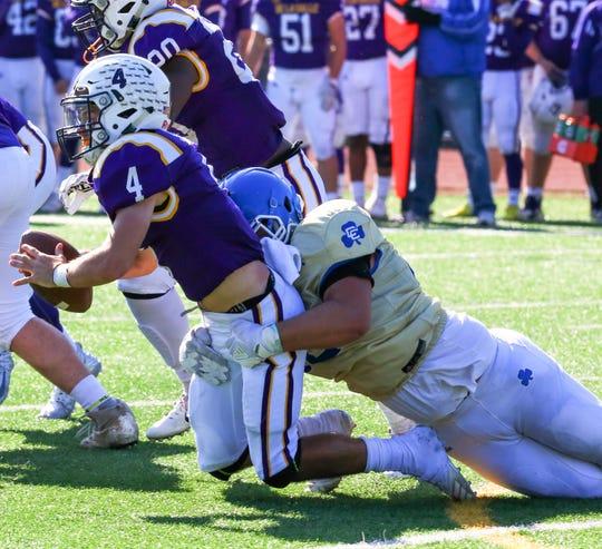 Catholic Central's Lucas Hendershot (right) sacks DeLaSalle quarterback Nolan Schultz.
