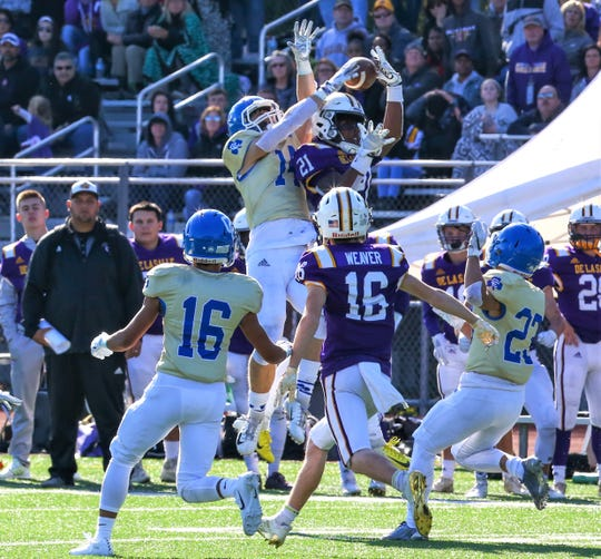 Catholic Central's Ryan Birney goes up and tips the ball away from DeLaSalle receiver Joshua DeBerry (21) during Sunday's Boys Bowl.