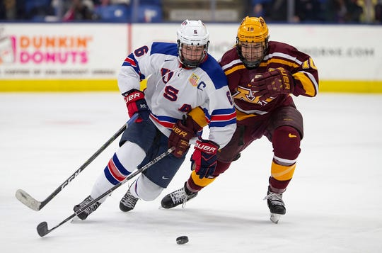 Jack Hughes (6) of the U.S. NTDP Under-18 team carries the puck ahead of Minnesota's Brent Gates Jr.