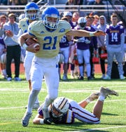 Catholic Central running back Keegan Koehler (21) tries to escape a DeLaSalle tackler in the Boys Bowl.
