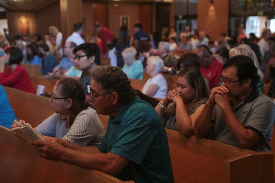 Parishioners receive Communion during Sunday Mass at Sacred Heart Catholic Church in Palm Desert, Calif., October 14, 2018. Monsignor Howard Lincoln addressed the sexual assault allegations against Peter McCormick, who was a priest at Sacred Heart from 1984 to 2000, during Mass.