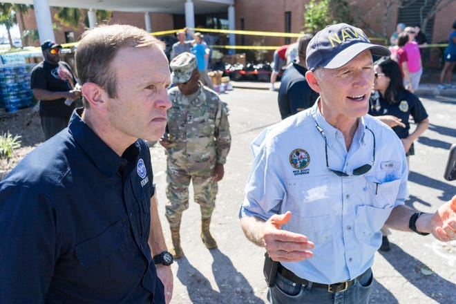 Brock Long, administrator of the Federal Emergency Management Agency, and Gov. Rick Scott speak with Hurricane Michael survivors before a church service Sunday at St. Andrew Baptist Church in Panama City.