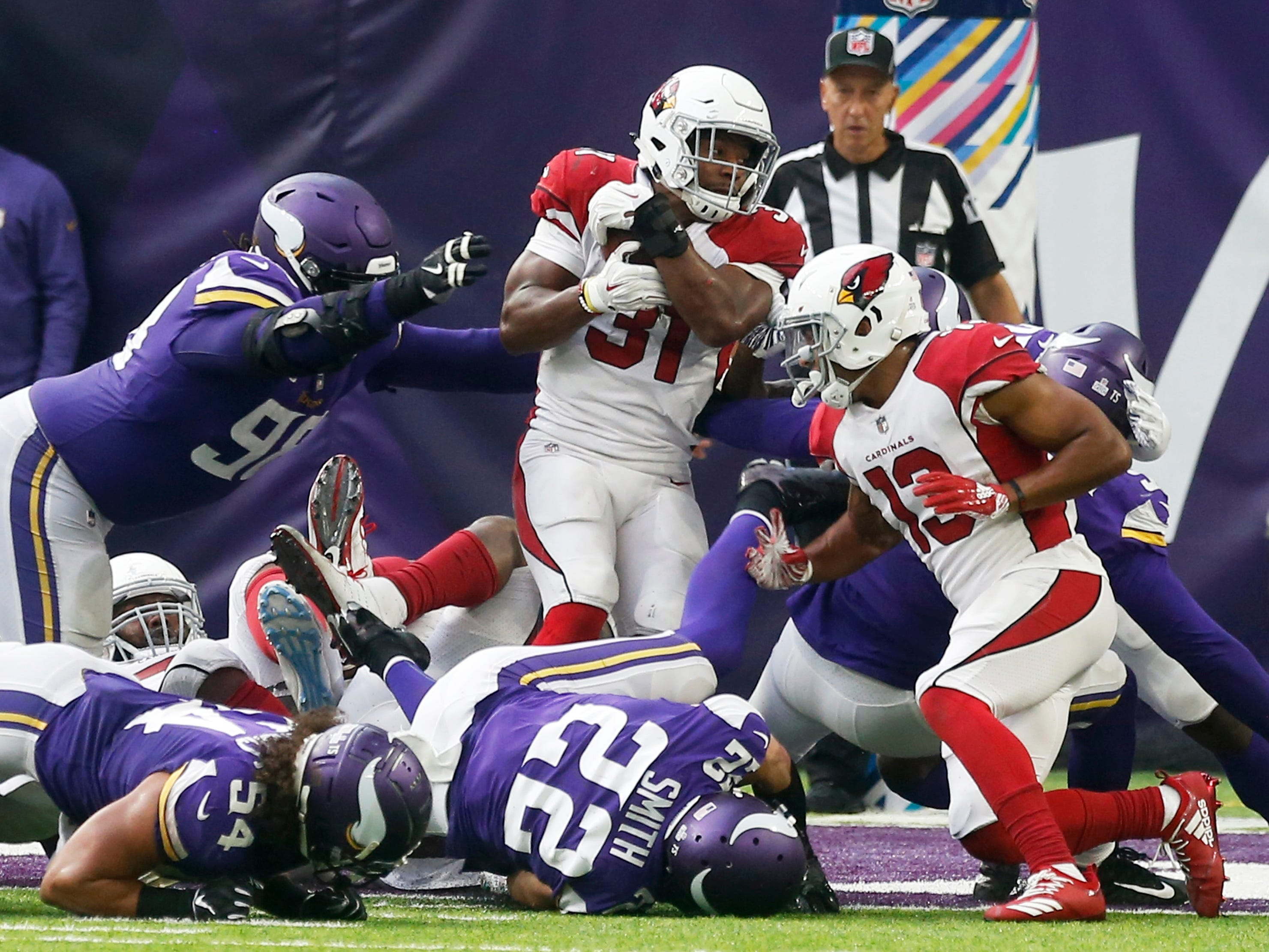 Arizona Cardinals running back David Johnson (31) scores on a 1-yard touchdown run ahead of Minnesota Vikings defensive tackle Linval Joseph, left, during the second half of an NFL football game, Sunday, Oct. 14, 2018, in Minneapolis. (AP Photo/Jim Mone)