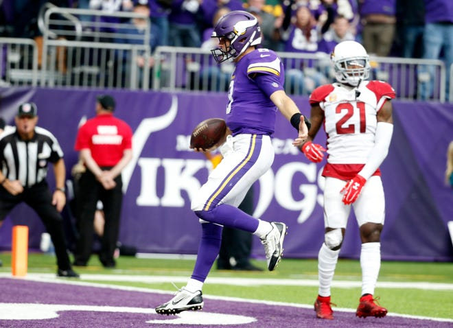 Minnesota Vikings quarterback Kirk Cousins scores on a 7-yard touchdown run in front of Arizona Cardinals cornerback Patrick Peterson (21) during the second half of an NFL football game, Sunday, Oct. 14, 2018, in Minneapolis. (AP Photo/Bruce Kluckhohn)